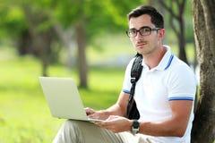 En högskolestudent som ser kameran, medan arbeta en uppgift Royaltyfria Bilder