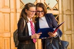 En högstadiumlärare talar till en kvinnlig student nära ytterdörren av skolan royaltyfria bilder