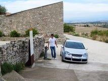 En högväxt stilig man klev ut ur hans bil till en dricka springbrunn på en tur till en sydlig terräng för stäpp Lantlig sommaröke royaltyfria foton