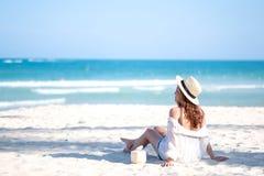 En h?rlig asiatisk kvinna tycker om att sitta och att dricka kokosn?tfruktsaft p? stranden arkivbild