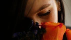 En h?rlig flicka kommer med en bukett av blommor till hennes n?sa och luktar dem som st?r p? f?nstret closeup arkivfilmer