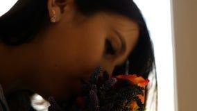 En h?rlig flicka kommer med en bukett av blommor till hennes n?sa och luktar dem som st?r p? f?nstret closeup lager videofilmer