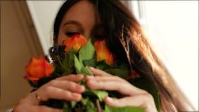 En h?rlig flicka kommer med en bukett av blommor till hennes n?sa och luktar dem som st?r p? f?nstret closeup stock video
