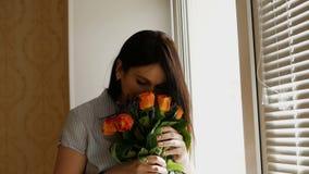 En h?rlig flicka kommer med en bukett av blommor till hennes n?sa och luktar dem som st?r p? f?nstret Skjutit medel lager videofilmer