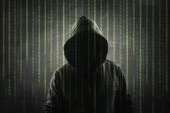 En hacker över en grön skärm med binär kod arkivbilder