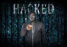 En hacker bak en maskering Arkivbilder