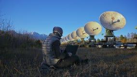 En hacker hackar radioteleskopet genom att använda anteckningsboken Man som programmerar att hacka på bärbara datorn i natur Terr stock video