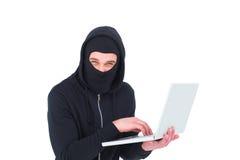 En hacker i balaclava genom att använda bärbara datorn för att stjäla identitet arkivfoto