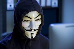 En hacker i en maskering av Guy Fawkes Arkivfoton