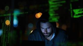 En hacker i ett mörkt rum som arbetar på en bärbar dator lager videofilmer