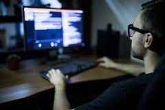En hacker i hörlurar med mikrofon och glasögon med tangentborddataintrångADB-systemet Royaltyfri Fotografi