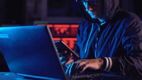 En hacker i huven som rymmer telefonen i hans h?nder som f?rs?ker att hacka mobil enhetmolnet i neonljus Abstrakt bakgrund med l? lager videofilmer