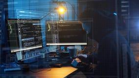 En hacker i maskering med datoren som gör cyberattack arkivfilmer