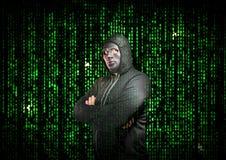 En hacker med armar som korsas bak en maskering Arkivfoto