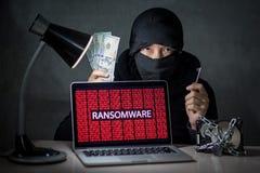 En hacker med att anfalla för ransomware för visning för datorskärm Arkivbild