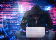 En hacker med ben korsade genom att använda en bärbar dator framme av digital bakgrund Royaltyfria Bilder