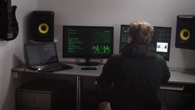 En hacker samlar olika datordata för att hacka databas Special utbildad ung man som arbetar för åtskilliga bildskärmar arkivfilmer