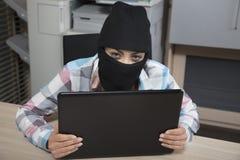 En hacker ser bakifrån en dator som ser dig Royaltyfria Bilder