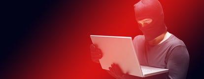 En hacker som använder bärbara datorn för att stjäla identitet arkivbild