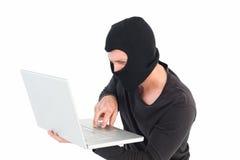 En hacker som använder bärbara datorn för att stjäla identitet royaltyfri bild