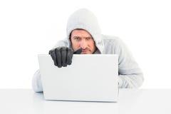 En hacker som använder bärbara datorn för att stjäla identitet royaltyfri fotografi
