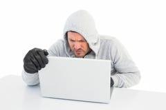 En hacker som använder bärbara datorn för att stjäla identitet royaltyfria foton