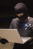 En hacker som använder bärbara datorn för att stjäla identitet royaltyfria bilder