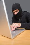 En hacker som använder bärbara datorn för att stjäla identitet royaltyfri foto