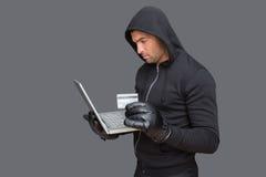 En hacker som använder bärbara datorn för att stjäla identitet arkivfoton