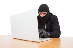 En hacker som använder bärbara datorn för att stjäla identitet fotografering för bildbyråer