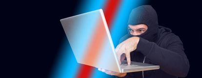 En hacker som använder bärbara datorn för att stjäla identitet på skrivbordet royaltyfri foto