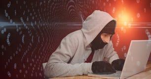 En hacker som använder bärbara datorn mot abstrakt bakgrund Arkivfoto