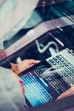 En hacker som använder datoren, smartphonen och att kodifiera för att stjäla lösenord a royaltyfri fotografi