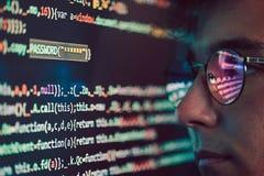 En hacker som använder datoren, smartphonen och att kodifiera för att stjäla lösenord a arkivfoto