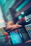 En hacker som använder datoren, smartphonen och att kodifiera för att stjäla lösenord a arkivbild