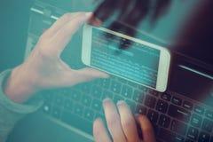 En hacker som använder datoren, smartphonen och att kodifiera för att stjäla lösenord a arkivfoton