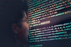 En hacker som använder datoren, smartphonen och att kodifiera för att stjäla lösenord a royaltyfria bilder