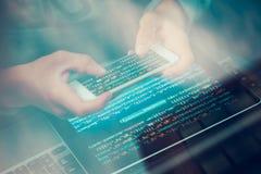 En hacker som använder datoren, smartphonen och att kodifiera för att stjäla lösenord a royaltyfri bild