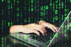 En hacker som använder tangentbordet som skriver dåliga data in i datoronline-syste Arkivfoton