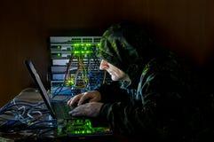 En hacker som arbetar på datoren med en hackerhjälpmedel Royaltyfri Fotografi