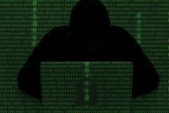 En hacker som bär en med huva överkant genom att använda bärbar datordatoren i mörkret T Royaltyfri Fotografi