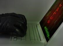 En hacker som bär svarta handskar genom att använda en bärbar dator Royaltyfria Bilder