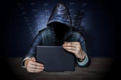 En hacker som gör spionage med bärbara datorn Arkivbild