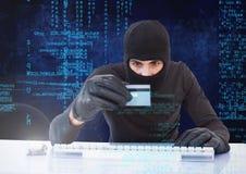 En hacker som rymmer en kreditkort och framme skriver på ett tangentbord av digital bakgrund fotografering för bildbyråer