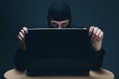 En hacker som stjäler data av en bärbar datordator Royaltyfria Foton