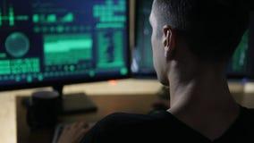 En hackerarbeten på datorer och drinkte i ett mörkt kontor hyr rum stock video