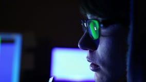 En hackerflickan arbetar på datoren och att röka den elektroniska cigaretten stock video