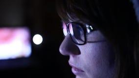 En hackerflickan arbetar på datoren och att röka den elektroniska cigaretten arkivfilmer