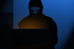 En hackerman i hoodieskjortamaskinskrivning som hackar global netwoksäkerhet royaltyfri bild