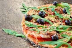 En halva av hemlagad vegetarisk pizza med ny rucola, tomater och svarta oliv på det svarta tabellslutet upp med utrymme för fri k Royaltyfri Bild
